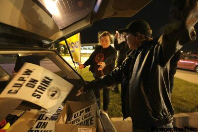 Canada Post workers gather picket signs from a car at the Canada Post processing facility in Winnipeg on Thursday night. About 150 workers in Winnipeg have taken to the picket line for the first in a series of rotating 24-hour strikes.