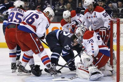 Winnipeg Jets forward Chris Thorburn loses his helmet in front of Washington Capitals goaltender Braden Holtby during the second period of an NHL game at the MTS Centre in Winnipeg on Thursday. The Jets wound up on the wrong end of a 4-0 score.