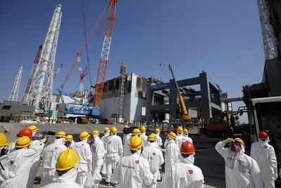 FILE - In this March 6, 2013 file photo, journalists wearing protective gears are escorted to the damaged No. 4 reactor building and an under construction foundation, center right, which will store the reactor's melted fuel rods, at Tokyo Electric Power Co.'s crippled Fukushima Dai-ichi nuclear power plant in Okuma town, Fukushima prefecture, northeast of Tokyo. The cooling system failed for a storage pool for fuel at one of the reactors at the tsunami-damaged nuclear plant in northeastern Japan Friday, April 5, 2013, - the second in a month, although there was no immediate danger from the breakdown. (AP Photo/Issei Kato, File)