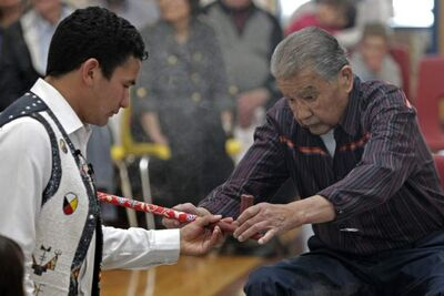 Wab Kinew, left, and his father Tobasonakwut prepare a ceremonial pipe during the adoption of James Weisgerber, the Archbishop of Winnipeg, in  April at Thunderbird House.