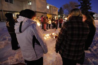 Friends and family attend a vigil Sunday in the courtyard of a Manitoba Housing complex on Doncaster Street where the body of a woman was discovered Saturday morning. While not confirmed by police, family members say the dead woman is Nadia Fiddler.