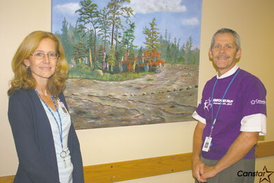 Rev. Kathleen Rempel Boschman, manager of spiritual care at Concordia Hospital, and Henry Tessmann, president and chief operating officer at Concordia Hospital in front of an art piece on display at the hospital.