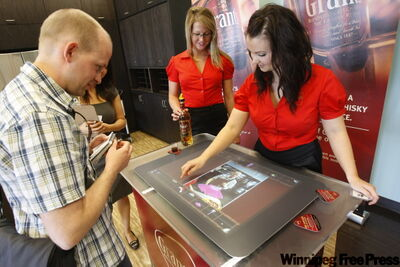 Winnipeg Free Press wine columist Ben MacPhee-Sigurdson (left) gets a firsthand look at the Grant's Whisky Microsoft Surface with company representative Kendall Bishop (center) and Vanessa Kunderman at the Madison Square MLCC location. Microsoft Surface is an interactive surface computing platform that provides access to digital content through natural gestures, touch and physical objects.