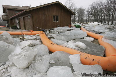 A home surrounded by ice sits empty on the bank of the Red River in St. Clements. Massive blocks of ice proved to be too much for temporary tube dikes as it was forced onto the shore at Breezy Point and St Clements, early Sunday morning.
