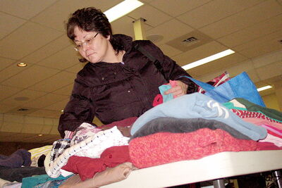 "A woman searches through a pile of clothes during the North End Family  Centre's ""Great Clothing Giveaway"" on March 2. The centre has had to put its popular clothing exchange program on hiatus due to lack of volunteers."