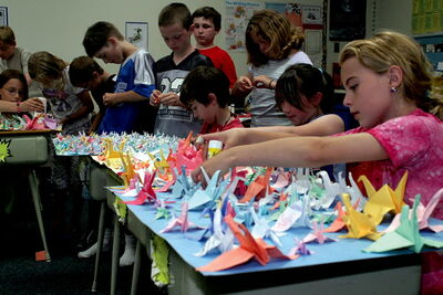 Grade 4 students at École Guyot make paper cranes in a file photo. École Guyot is receiving money from the provincial government to fund a natural playground, 500 feet of walking and biking paths, and other upgrades.