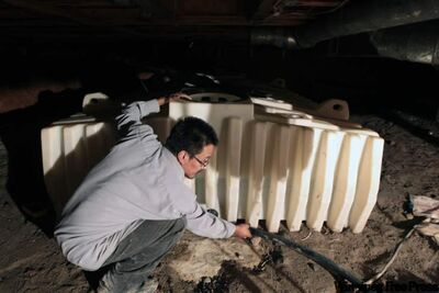 Garden Hill's Little family has a contaminated cistern that made family members sick. Water treatment plant operator Bruce McDougall checks the storage tank in a crawl space under the home.