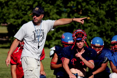 Head coach of the Churchill Bulldogs Tom Wall runs his team through some tackling drills Aug. 22 preparing for their trip to New York.