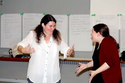 Hope McIntyre (left) and co-facilitator Kerri Potter share a laugh during a drama session for an upcoming production called Giving Voice.