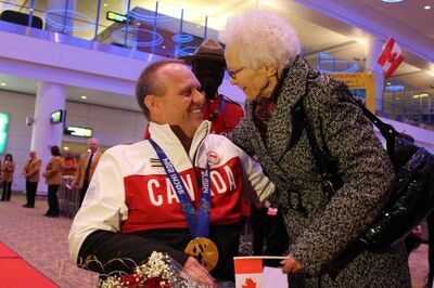Dennis Thiessen gets a hug from his mother Tina Thiessen after his return from Sochi on March 18.