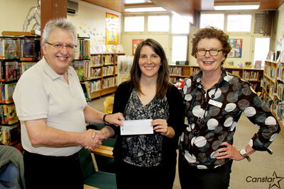 L–R: Bill Zuk, Winnipeg Public Library Board, presents a cheque to Henry G. Izatt Middle School Teacher-Librarian Brandi Nicholauson and Fort Garry Library branch head Jane Bridle. The middle school is holding a project, entitled Encouraging Reluctant Readers with Graphic Novels, this April in conjunction with the library. The library board awarded a $1,500 grant for the initiative.