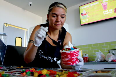 Michelle Kindrat scoops some candy on a bowl of frozen yogurt. Kindrat, along with her husband Jeff, opened their Spoon Me franchise at 2705 Main St. on July 18.