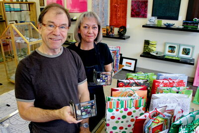 Brian McMillan and Heather Harris of Prairie Stained Glass take a break from gift-wrapping 40 handmade candle holders the business and its artists donated to Winnipeg Harvest last week.
