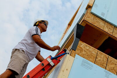 A Habitat volunteer helps direct a section of housing into place at a build in Riverbend earlier this summer.