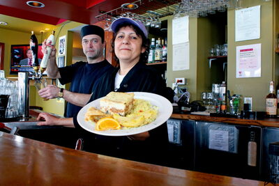As Bill Parasidis pours a pint, Kathy Makris serves up a plate of her homemade moussaka, spanakopita, tyropita and famous Greek roasted lemon potatoes. Makris recently took over the kitchen at the Nook & Cranny.