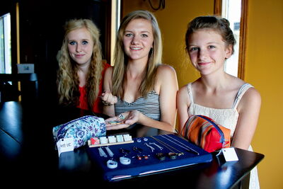 Lauren Wittman (centre) her cousin Zoee (left) and sister Jenna show off some of the jewelry they've made reusing old film negatives, plastic milk jugs, and Scrabble game tiles they say would otherwise end up in the garbage.