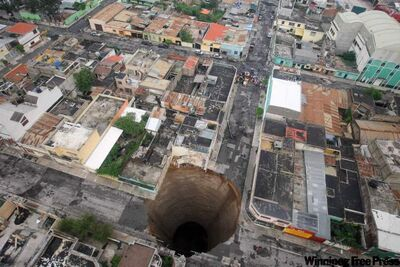In this photo released by Guatemala's Presidency on Monday May 31, 2010, a  sinkhole covers a street intersection in downtown Guatemala City, Monday May 31, 2010.