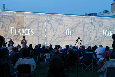 Audience members sit on the lawn of The Historical Museum of St. James last Saturday in front of a brick wall used to screen Flames of War.