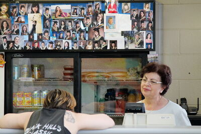 "A student flops in dramatic despair on the lunch counter at John Taylor last Thursday, asking Nicki Douklias (right) why she has to retire.The student pictures behind Douklias are going home with her and will be with her ""forever,"" she said."