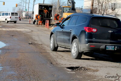 A car weaves around potholes on Berry Street next to the Hilton Suites hotel last Wednesday. Water main workers said they put gravel in some of the worst holes for their own safety.