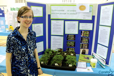 Ilsa Chaytor smiles alongside the greenery that earned her a trip to Lethbridge for the national fair in May. She resolved questions about how much daylight indoor plants should receive.