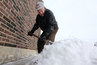 Bill Andrusiak, 80, shovels snow from the front of his hardware store at the corner of Aberdeen Avenue and Arlington Street on Sunday. His father opened Andrusiak Hardware in 1920.