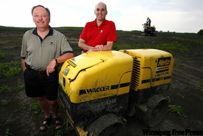 Brent Kerslake (left), Mike Kenney of Southwood Golf and Country Club lean on a compactor used to help transform flat prairie into a sculpted, rolling golf course.