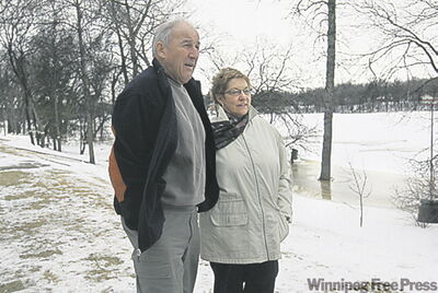 Marge and Ted Avent gaze at the Red River from the dike in their Winnipeg backyard.