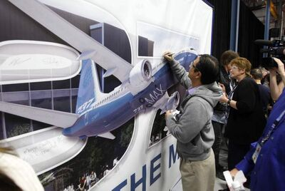Boeing Canada employees sign a banner after the announcement of the expansion of the Winnipeg plant Tuesday.