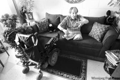 Nick Ternette holds forth on the couch in his apartment. He says he misses his strong voice more than his legs -- his wheelchair has replaced them.