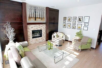 A cultured stone wall with gas fireplace in the centre is surrounded by custom maple-stained walls.