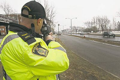 Const. Ray Howes of the Winnipeg Police Service shows use of traditional laser speed gun near the intersection of Grant and Nathaniel.