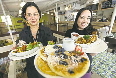 Food co-ordinator Talia Syrie (left) and Jade McIvor offer some fluffy blueberry pancakes and poutine.