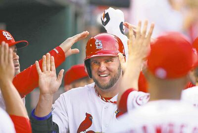 Matt Adams of the Cardinals is congratulated after scoring on Yadier Molina's double during the sixth inning in Game 1 on Thursday.