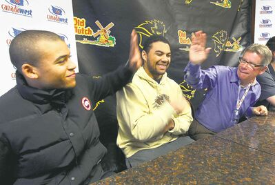 University of Manitoba head coach Brian Dobie (right) high-fives star RB Anthony Coombs while an amused Nic Demski looks on during Thursday's news conference.