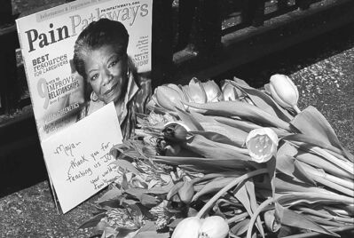 A bouquet of flowers and a magazine showing Angelou on the cover lies outside a gate at her home in Winston-Salem, N.C., on Wednesday.