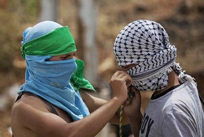 A Palestinian, identified by his green headband as a supporter of Hamas, helps a fellow protester cover his face with the black-and-white scarf that has become a symbol of the Fatah movement outside Ofer, an Israeli military prison near the West Bank city of Ramallah, Wednesday, June 4, 2014. Hamas and Fatah have been longtime rivals, but last week formed a unity government.