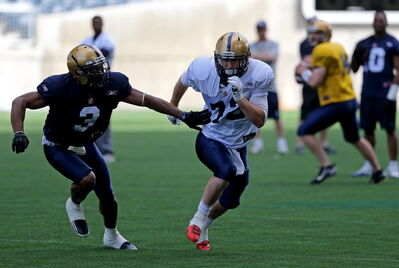 Winnipeg Blue Bombers' Cauchy Muamba (3), tries to hold up Brett Carter (72) while he waits for a pass from QB, Chase Clement (14), right, during practice at Investors Group Field Saturday.