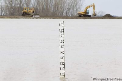 A marker measures the water level in the Portage Diversion near Portage la Prairie Friday as heavy machinery work to heighten the dike as the water level increases. THE CANADIAN PRESS/