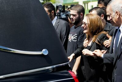 "Sahar Bahadi (centre), mother of Sammy Yatim, cries as she follows the hearse carrying the casket of her son at his funeral in Toronto on Thursday, August 1, 2013. Yatim died Saturday morning after receiving multiple gunshot wounds during an ""interaction"" with police. THE CANADIAN PRESS/Nathan Denette"