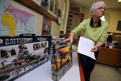 Dianne Cooper from Project Peacemakers displays violent and non-violent toys at Westminster United Church, Saturday.