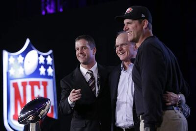 49ers' head coach Jim Harbaugh (left) and Ravens' head coach John Harbaugh (right) share centre stage Friday with their pop, Jack.