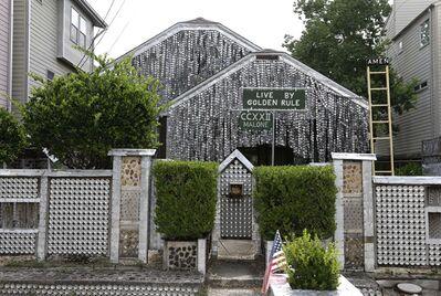 The beer can house, a Houston landmark, sits between newer homes Wednesday, July 10, 2013, in Houston. Former owner John Milkovisch covered the outside on the house with siding made of cut and flatten beer cans and garlands made from the lids. The Orange Show Center for Visionary Art, a local nonprofit that preserves art installations in the city, bought the property about 10 years ago, restored the house and it opened it to the public. (AP Photo/Pat Sullivan)