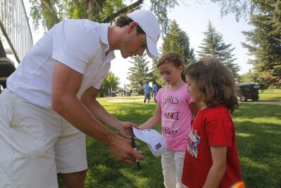 Jonathan Toews signs his autograph for two fans.
