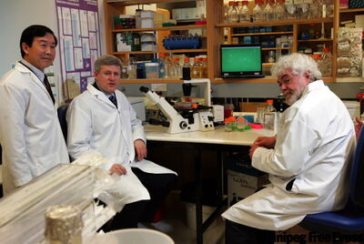 Prime Minister Stephen Harper tours Canada's National Microbiology Laboratory  in Winnipeg with (right) Dr. Frank Plummer, Scientific Director General. He stopped in the Level 2 lab with Dr. Yan Li (left), Chief of the Influenza and Respiratory Viruses Section which is doing research on the H1N1 flu virus.