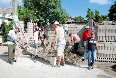Funk (centre) and workers mix concrete during construction of the cinder block building.