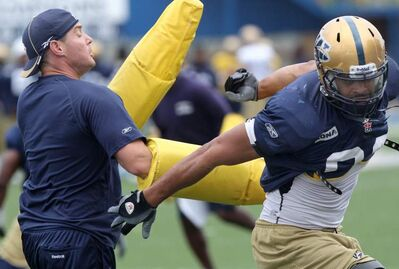 Winnipeg Blue Bomber's Jason Vega gets put through the paces by Casey Creehan during  practice at  Canad Inns Stadium on Aug. 30, 2011.