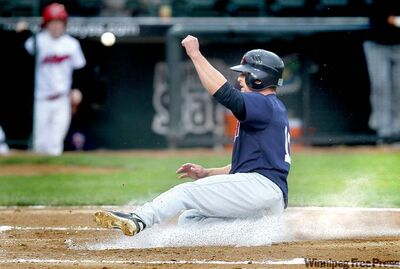 Goldeyes' Kody Kaiser slides home just in front of the ball to score the first run at a pre-season game Monday night. Fish won 7-3 against the St. Paul Saints.