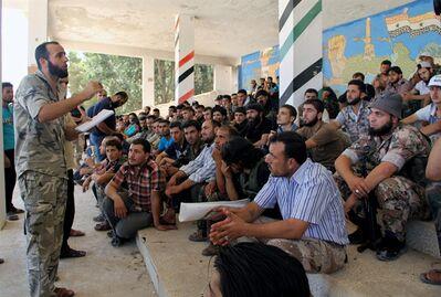 In this Tuesday, Aug. 13, 2013 citizen journalism image provided by Tawhid Brigade, which has been authenticated based on its contents and other AP reporting, Abdul-Qadir Saleh, left, the chief commander of the Tawhid Brigade, the main rebel outfit in Aleppo province, speaks to his fighters ahead of an attack on government troops, in Aleppo, Syria. The Britain-based Syrian Observatory for Human Rights, which relies on a network of activists on the ground, said Friday that a government airstrike the previous night in northern Syria killed a senior rebel figure and wounded two commanders and the spokesman of the Tawhid Brigade. According to the Observatory, the chief commander of the brigade, Abdul-Qadir Saleh, was wounded while the brigade's financial officer, Abu Tayeb, was killed. (AP Photo/Tawhid Brigade)