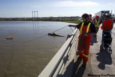 Workers with Water Survey of Canada monitor the flow rate in the Portage Diversion as they monitor flood waters from the Assiniboine River on Tuesday.